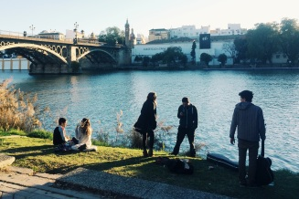 College students by the river in Sevilla, Spain
